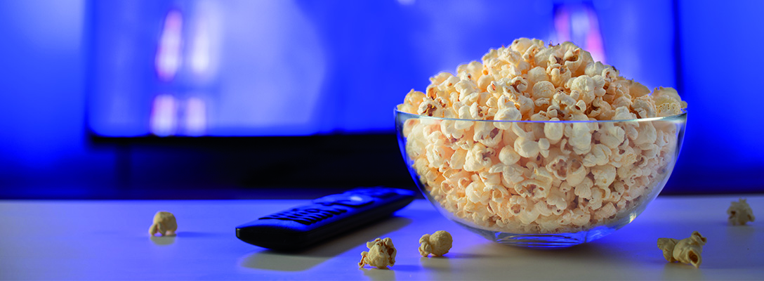 Bowl of Popcorn in Front of TV with Sports Movie